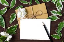 Cartão e envelope vazios com flores do jasmim, lápis e as folhas verdes Fotos de Stock Royalty Free