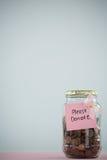 Cartão e fita cor-de-rosa da conscientização do câncer da mama no frasco com as moedas na tabela Imagem de Stock
