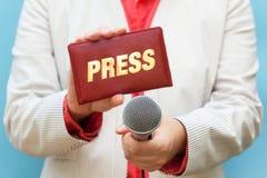 Cartão e microfone fêmeas de imprensa da terra arrendada do journalista imagens de stock royalty free