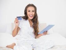 Cartão e tabuleta morenos atrativos alegres de crédito da sustentação fotos de stock royalty free