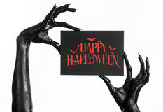 Cartão e tema feliz de Dia das Bruxas: a mão preta da morte que guarda um cartão de papel com as palavras Dia das Bruxas feliz em imagem de stock