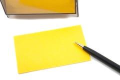 Cartão (em branco) amarelo do negócio no branco com pena Foto de Stock