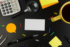 Cartão em branco branco Mesa da tabela do escritório com grupo de fontes coloridas, copo, pena, lápis, flor, notas, cartões sobre Imagens de Stock Royalty Free
