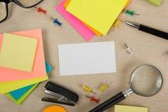 Cartão em branco branco Mesa da tabela do escritório com grupo de fontes coloridas, copo, pena, lápis, flor, notas, cartões sobre Fotografia de Stock Royalty Free