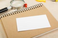 Cartão em branco branco Mesa da tabela do escritório com grupo de fontes coloridas, copo, pena, lápis, flor, notas, cartões sobre Fotografia de Stock