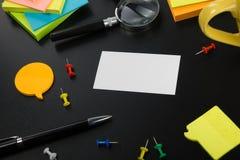 Cartão em branco branco Mesa da tabela do escritório com grupo de fontes coloridas, copo, pena, lápis, flor, notas, cartões sobre Fotos de Stock