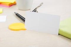 Cartão em branco branco Mesa da tabela do escritório com grupo de fontes coloridas, copo, pena, lápis, flor, notas, cartões sobre Fotos de Stock Royalty Free