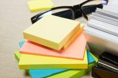 Cartão em branco branco Mesa da tabela do escritório com grupo de fontes coloridas, copo, pena, lápis, flor, notas, cartões sobre Foto de Stock Royalty Free