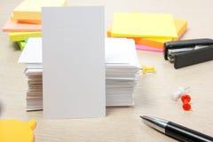 Cartão em branco branco Mesa da tabela do escritório com grupo de fontes coloridas, copo, pena, lápis, flor, notas, cartões sobre Imagens de Stock
