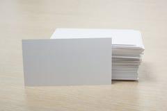 Cartão em branco branco Mesa da tabela do escritório com grupo de fontes coloridas, copo, pena, lápis, flor, notas, cartões sobre Foto de Stock