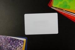 Cartão em branco branco Mesa de escritório com grupo de fontes coloridas, copo, pena, lápis, flor, notas, cartões no preto Imagem de Stock Royalty Free