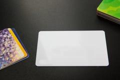 Cartão em branco branco Mesa de escritório com grupo de fontes coloridas, copo, pena, lápis, flor, notas, cartões no preto Fotografia de Stock Royalty Free