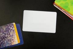 Cartão em branco branco Mesa de escritório com grupo de fontes coloridas, copo, pena, lápis, flor, notas, cartões no preto Fotos de Stock Royalty Free