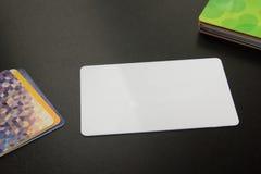 Cartão em branco branco Mesa de escritório com grupo de fontes coloridas, copo, pena, lápis, flor, notas, cartões no preto Foto de Stock