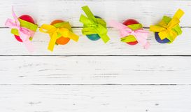 Cartão feliz colorido da Páscoa com os ovos da páscoa coloridos no fundo de madeira branco da tabela Fotos de Stock