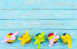 Cartão feliz da Páscoa com beira colorida dos ovos na luz - tabela de madeira azul, vista superior, espaço da cópia Foto de Stock Royalty Free