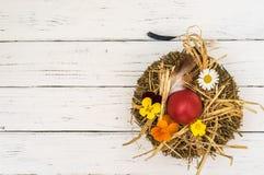 Cartão feliz da Páscoa com ovo da páscoa, palha e flores na tabela de madeira branca, vista superior com espaço da cópia Fotos de Stock Royalty Free