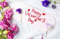 Cartão feliz do dia de Valentim com as flores no branco foto de stock royalty free