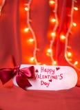 Cartão feliz do dia de Valentim contra o fundo vermelho imagem de stock