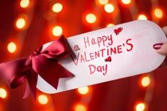 Cartão feliz do dia de Valentim contra o fundo vermelho imagens de stock royalty free