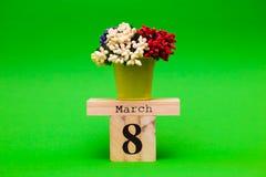 Cartão feliz do dia do ` s da mulher uma cubeta pequena das flores e do calendário de madeira Imagem de Stock