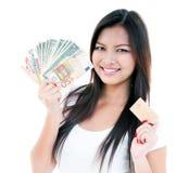 Cartão feliz do dinheiro e de crédito da terra arrendada da mulher nova imagens de stock