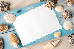 Cartão marinho do verão Conchas do mar em placas de madeira azuis na areia na praia Foto de Stock
