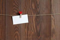 Cartão para registros com um clothespeg de madeira com coração vermelho em uma corda Fotografia de Stock Royalty Free
