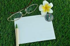 Cartão, pena, vidros, compasso e frangipani na grama Imagens de Stock Royalty Free