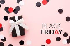 Cartão preto de sexta-feira com caixa de presente e confetes no fundo cor-de-rosa fotografia de stock royalty free