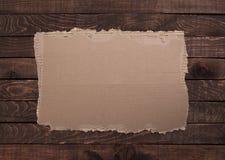 Cartão rasgado na textura de madeira Fotos de Stock