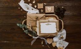 Cartão vazio com as decorações do envelope e do ouro de kraft no fundo de madeira Conceito do casamento fotografia de stock