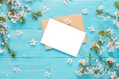 Cart?o vazio com as flores da cereja da mola no fundo de madeira azul Configura??o lisa Vista superior Zombaria acima Conceito da fotos de stock royalty free