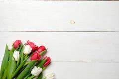 Cartão vazio com as flores das tulipas na tabela de madeira branca Cartão de casamento romântico, cartão para a mulher ou dia de