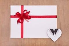 Cartão vazio com fita vermelha e coração branco Foto de Stock