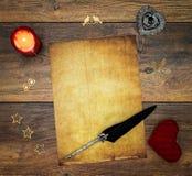 Cartão vazio do vintage com vela vermelha, o cervo vermelho do afago, as decorações de madeira, a tinta e a pena no carvalho do v imagem de stock