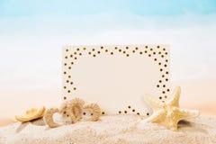 Cartão vazio, estrela do mar, coração na areia contra o mar fotos de stock