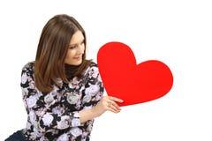 Cartão vermelho do dia de Valentim do coração do iwith da jovem mulher nas mãos Imagens de Stock Royalty Free