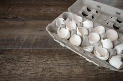 Cartón de cáscaras de huevo quebradas en el tablero de madera del tablón Fotos de archivo