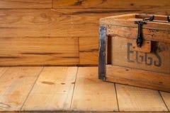 Cartón de huevos en el fondo de madera Foto de archivo libre de regalías