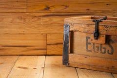 Cartón de huevos en el fondo de madera Imagen de archivo