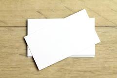 Cartões brancos vazios em um fundo de madeira claro Modelo para a identidade de marcagem com ferro quente Fotos de Stock