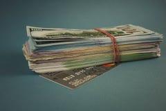 Cartões de crédito e um pacote de dinheiro em um fundo azul liso imagens de stock royalty free