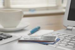 Cartões de crédito em um portátil com indicações do cartão de crédito um o copo de ho Fotos de Stock