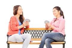 Cartões de jogo adolescentes das irmãs assentados em um banco Imagem de Stock Royalty Free