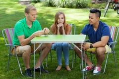 Cartões de jogo dos amigos em um jardim Imagem de Stock Royalty Free