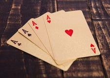 Cartões de jogo dourados quatro áss na placa de madeira Imagem de Stock Royalty Free