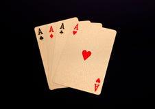 Cartões de jogo dourados quatro áss no fundo preto Fotografia de Stock Royalty Free