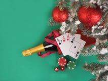 Cartões de jogo e microplaquetas de pôquer perto de uma árvore de Natal Imagem de Stock Royalty Free