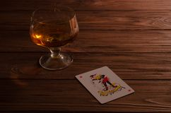 Cartões de jogo e vidro de vinho do conhaque na tabela de madeira foto de stock
